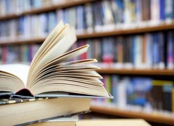 Sayfaları açık kitap ve kitaplık