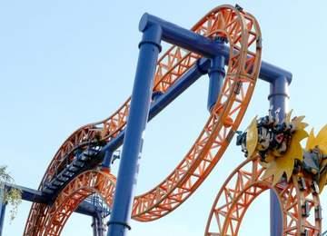 turuncu ve sarı renkte, hareket halindeyken tam ters dönmüş durumda olan bir roller coaster.