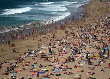 Kalabalık bir plajın yukarıdan görüntüsü.